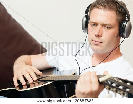 Handsome man with headphones playing the guitar.