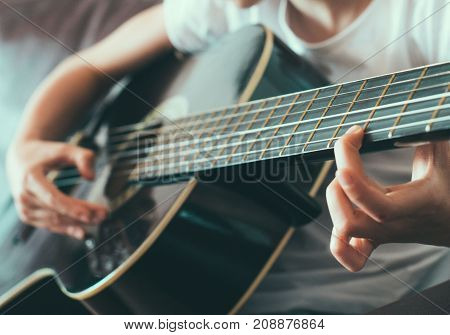 Little girl playing the guitar at home.