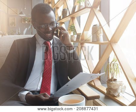 Horizontal Picture Of Dark-skinned Executive Male In Formal Clothes Spending Free Time In Cafe Indoo
