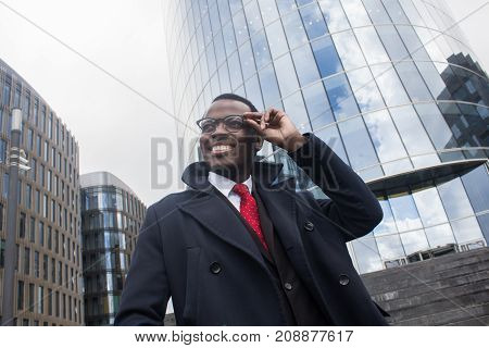 Street Closeup Of Young Handsome African American Businessman Walking Alone In City Center With Skys