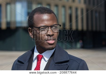 Urban Portrait Of African American Businessman Walking Alone In City Center Dressed In Dark Coat And