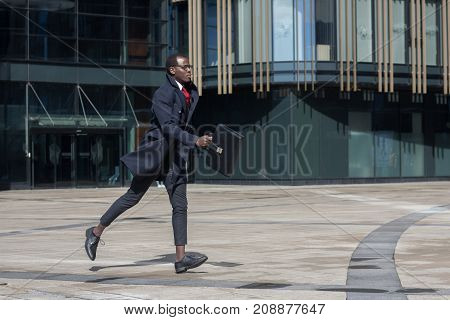 Full-length Portrait Of Dark-skinned African Entrepreneur Wearing Black Coat And Formal Clothes, Run
