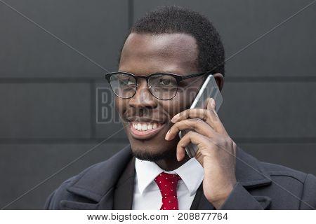 Horizontal Headshot Of Handsome Dark-skinned Entrepreneur Standing Against Grey Background Looking L