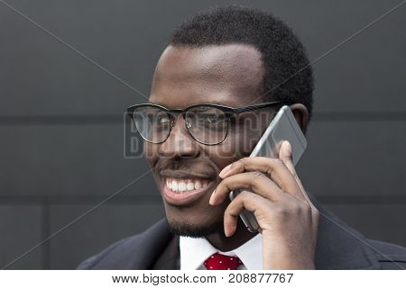 Closeup Portrait Of Handsome African Male Standing Isolated Against Grey Wall Wearing Formal Clothes