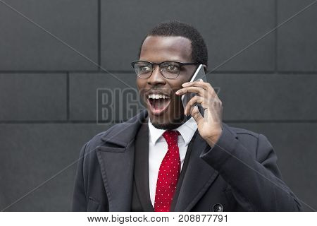 Outdoor Portrait Of Young African Male Standing In Street In City Center Dressed In Formal Suit, Whi