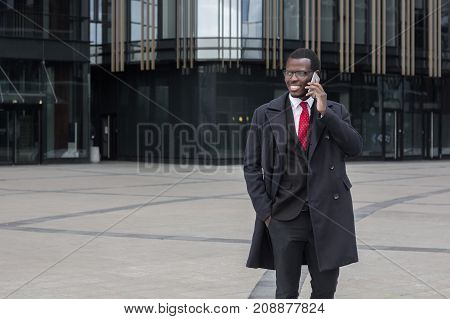 Full Length Portrait Of Handsome African Entrepreneur Pictured Outdoors In Street Dressed In Formal