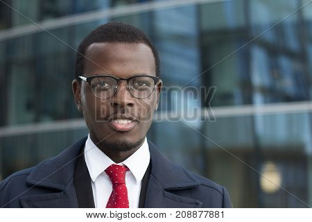 Outdoor Closeup Of African American Entrepreneur Pictured In Street With High Glass Building In Back