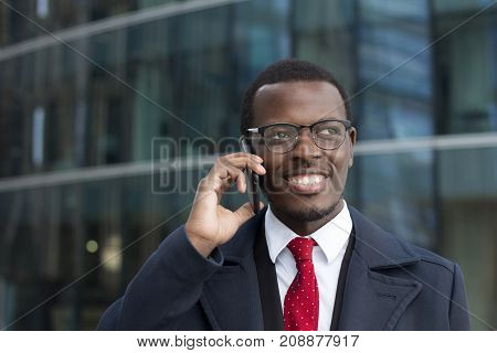 Urban Image Of Handsome African Entrepreneur Spending Break Outside High City Building Looking Aside