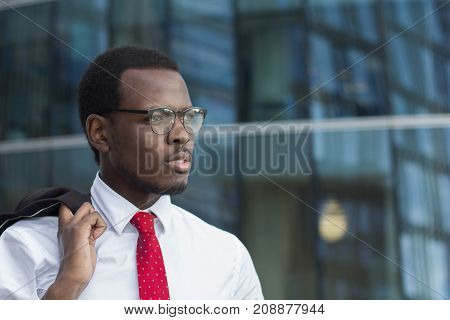 Horizontal Image Of Dark-skinned African Guy Standing Outdoors In White Shirt With Coat Hanging On F