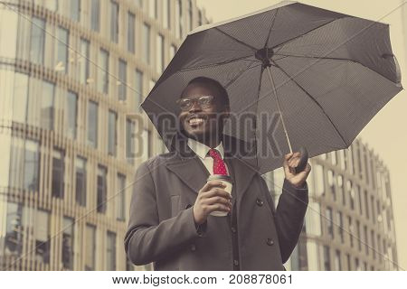 Urban Portrait Of Handsome African American Businessman Standing In City Center In Cloudy Weather Un
