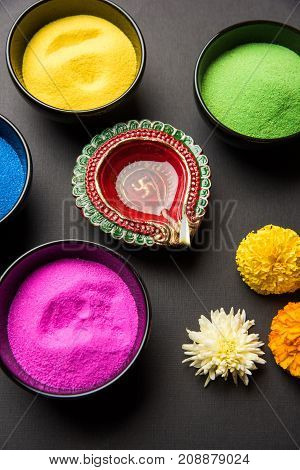 Stock Photo of happy diwali greeting card clicked using elements of Diwali festival like colourful rangoli in bowls, diwali clay lamp or diya and flowers