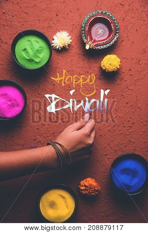 Stock Photo of happy diwali greeting card clicked using elements of Diwali festival like colourful rangoli in bowls, diwali clay lamp or diya and girl or girl making rangoli, writing happy diwali