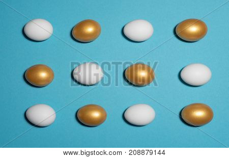 Concept of individuality exclusivity better choice. Pattern of white and gold eggs on blue background.
