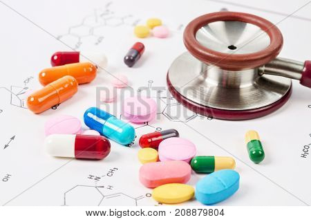 Heap of color pills and tablets with stethoscope medical on chemical formulas background.