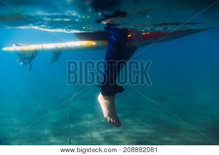 Surfer relax on surfboard in underwater. Surfer and ocean