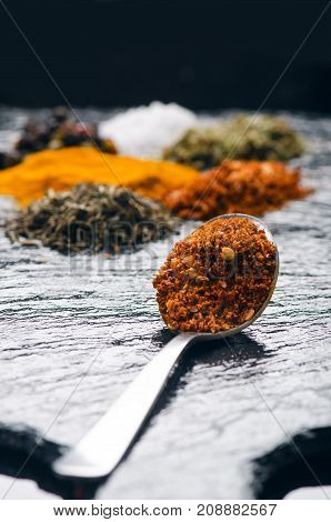 Different spices and herbs on a black slate. Iron spoon with chili pepper. Indian spices. Ingredients for cooking. Healthy eating concept. Various spices on dark background.