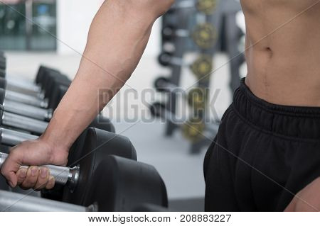 Young Man Execute Exercise In Fitness Center. Male Athlete Choose Dumbbell In Gym. Sporty Guy Workin