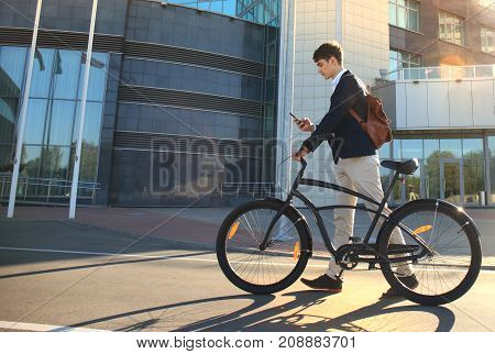 Young businessman with bicycle and smartphone on city street