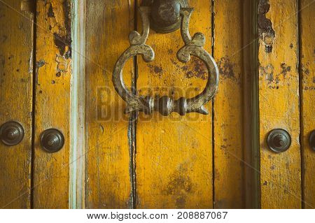 vintage retro style yellow wood door. old grunge brass doorknob. abstract background