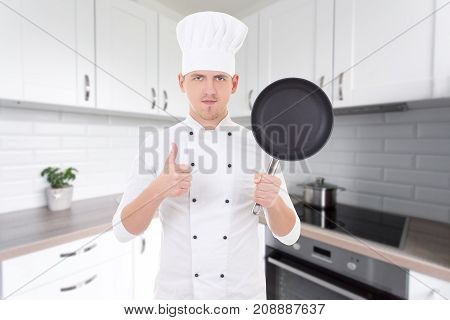 Man Chef In Uniform With Frying Pan In Modern Kitchen