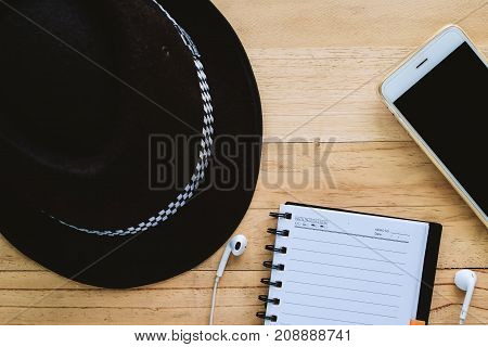 Blank page with black hat smartphone and earphone on the wooden table for taking note of good memories during the trip