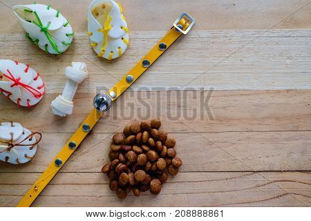 Dog snacks yellow collar and pellet food on wooden background with copyspace