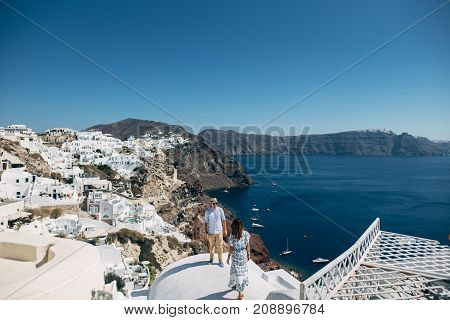 The Couple Is Standing On The Roof In Santorini