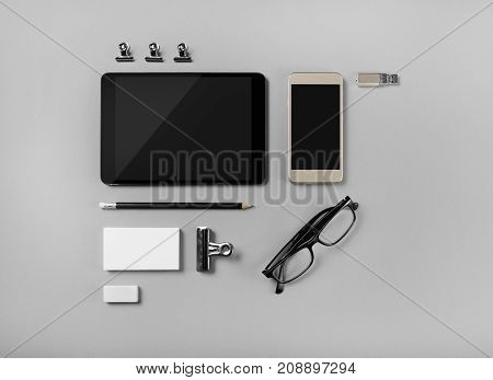 Mobile devices and blank stationery on gray paper background. Branding template. Objects for placing your design. Top view.