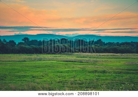 Afternoon beautiful summer landscape. Green grass and colorful sky with mountains in the background.