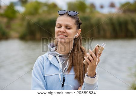 Young smiling woman in excellent spirits on the river bank with a phone listens to music on headphones with close eyes