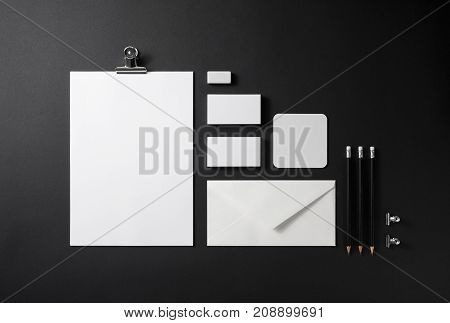 Brand identity mockup. Blank corporate stationery set on black paper background.