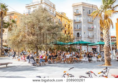 BARCELONA, SPAIN - August 16, 2017: View on the old buildings and coastline bars and restaurants full of people on Barcelonetas beach in Barcelona