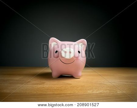 Piggy Bank Savings Currency concept : Pink piggy bank with smile face on wooden table with black background