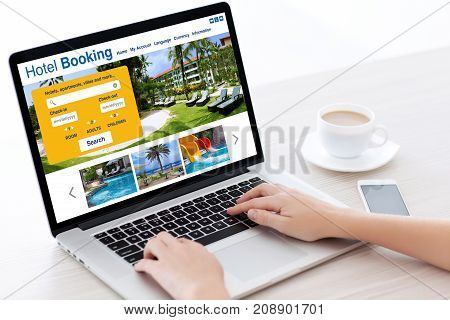 Female hands laptop keyboard with online search booking hotel on screen in white room