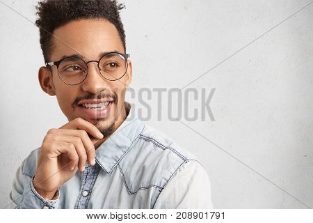 Intelligent Clever Male Student Wears Round Spectacles, Thinks Over Future Project, Looks Thoughtful