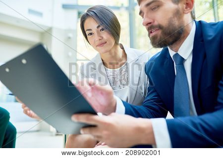 Bearded middle-aged manager holding clipboard in hands while sharing business ideas with pretty female colleague, she listening to him with interest