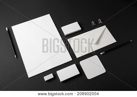 Blank stationery set with plenty of copy space for placing your design. Corporate identity mockup on black paper background.