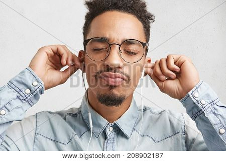 Horizontal Portrait Of Relaxed Fashionable Male Teenager With Beard And Mustache, Wears Big Spectacl