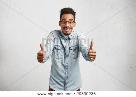 Overjoyed Young Male With Shaggy Hair, Mustache, Raises Thumbs, Shows Ok Sign, Being Delightful With