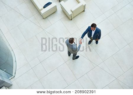 Directly above view of confident business partners shaking hands after successful completion of negotiations, interior of spacious office lobby