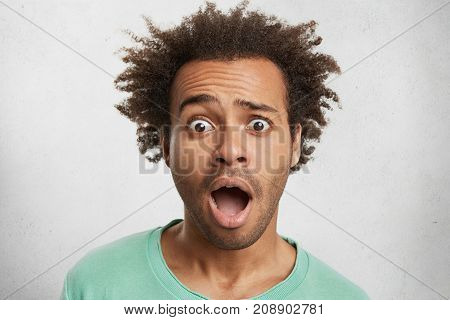 Headshot Of Scared Horrified Timorous Man Looks With Bugged Eyes As Sees Car Accident, Dressed Casua