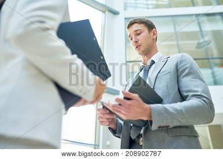 Low angle view of handsome young businessman presenting ideas to female colleague while having informal working meeting at office lobby