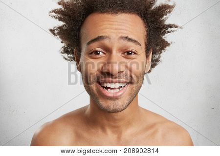 Headshot Of Pleasant Looking Male Guy With Shaggy Hairstyle, Bristle, Smiles Happily, Shows White Pe