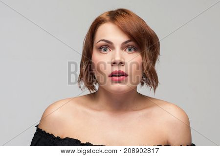 Astonished young female. Shocking news. Surprising gossip, beautiful amazed woman on grey background, daze concept