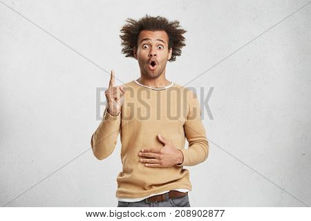 Horizontal Shot Of Astonished Man With Bushy Hairstyle Raises Fore Finger Up, Indicates On Something