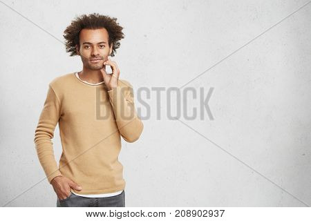 Handsome African American Unshaven Man With Bushy Hair, Has Confident Expression, Keeps Hand In Pock