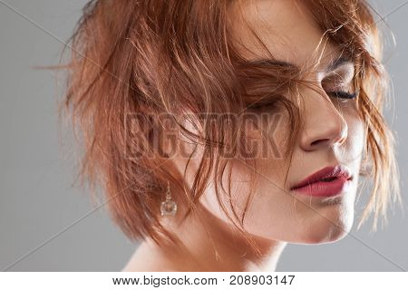 Dream life. Creative hairstyle commercial. Seductive young female, modern haircut for women closeup. Beauty relaxed girl on grey background, style concept
