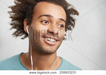 Carefree Clever Student With Bristle, Afro Hairstyle, Listens To Audio Lecture In Earphones, Uses Mo