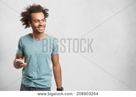 Horizontal Shot Of Handsome Teenager Dressed Casually, Holds Modern Smart Phone, Listens Melodies In