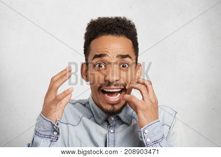 Scared Shocked Dark Skinned Man Gestures In Anxiety, Looks With Widely Opened Mouth And Bugged Eyes,